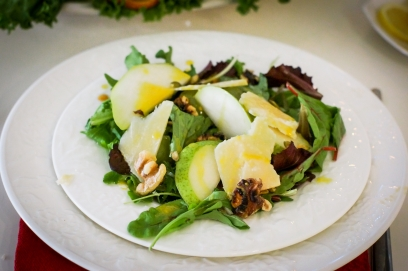 Salad with pears,walnuts and cheese on white plates